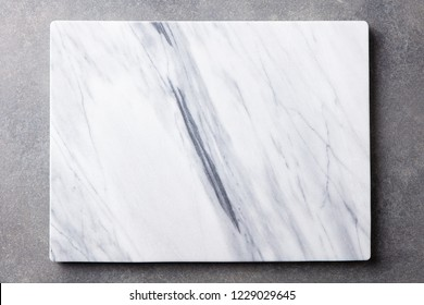 White marble texture board on grey background. Top view. Copy space.