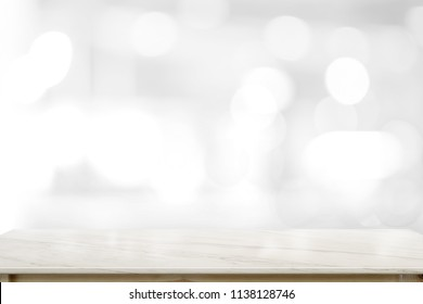 White marble top table over blurred white bokeh background.