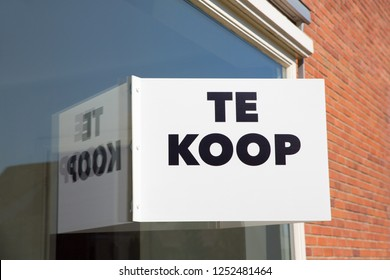 White marketing board on window of home with text Te Koop or For Sale