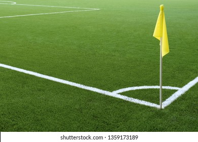 White markings on green grass and yellow flag. Corner of a football field. No people and players. Sports concept.