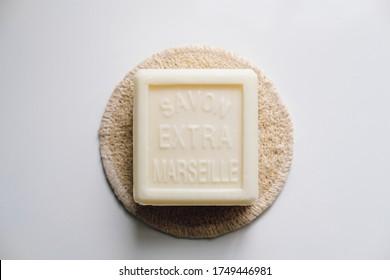 White Marseille soap on a loofah coaster