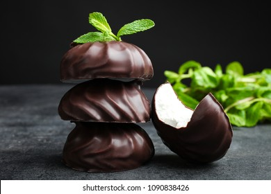 White marshmallow in chocolate and a mint leaf on a black background.