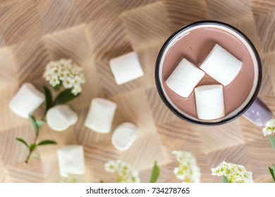 White marshmallows on top of hot cocoa in pink cup.  Fresh white spring flowers and more marshmallows are scattered around the cup. Cozy home concept. The view from above