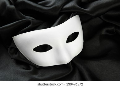 White mask, on black silk fabric