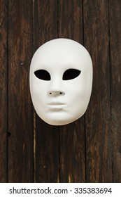White mask on wooden background
