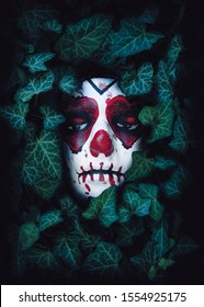 White mask of a woman face with hearts on the eyes and a sewn mouth at an ivy bush.