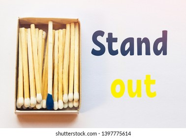 White matches and one match of blue color in a box. Difference, self respect and acceptance concept. Motivational phrase on the image. Opposition, uniqueness, individualism concept. Not alike.