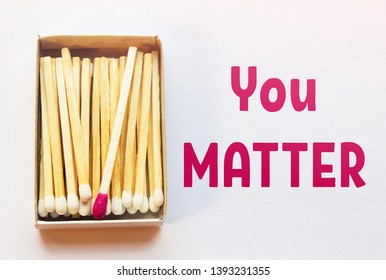 White matches and one match of crimson color in a box. Difference, self respect and acceptance concept. Motivational phrase on the image. Opposition, uniqueness, individualism concept. Not alike.