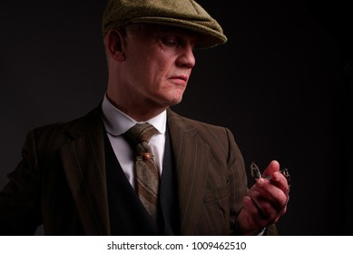 White mature male, gangster type, dressed in 1940s fashion looking at his watch.