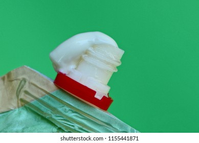 white mayonnaise on the neck of a plastic bag on a green background