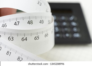 White measurement tape roll with number of centimeter and inch with calculator on white background with copy space using as health, diet or measuring tool concept.