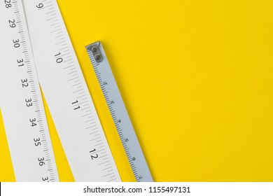 White measuring tapes with centimetre and inches on vivid yellow background with copy space, length, long or maker concept.