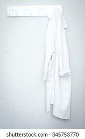 White medical coat laboratory uniform in hospital clinic on wall on coat hangar.