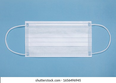 White medical mask isolated on blue background. Medical mask protection against pollution, virus, flu, coughing and coronavirus. Health care and surgical concept.