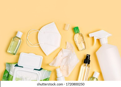 White medical masks and respirators with antibacterial wet wipes, disinfection spray and hand sanitizer on yellow background. Personal hygiene product for protection virus, flu, coronavirus, COVID-19