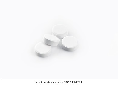 White medical pills isolated on a white background. Aspirin. Close-up