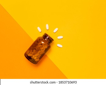 White medical pills and tablets spilling out of a amber glass bottle. Medicine creative concepts. Yellow and orange background. Flat lay top view