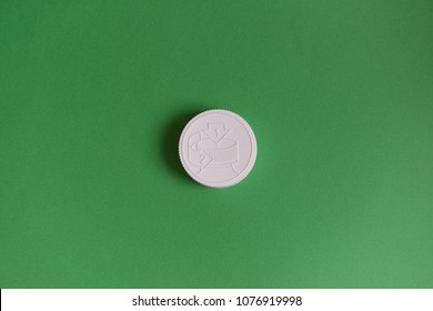 White medicine bottle cap child proof on green background. Medicine and health concept.