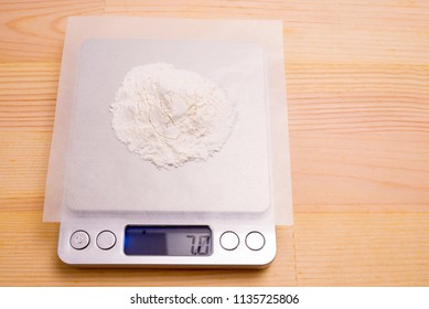 White medicine powder on paraffin paper weighed with electronic scale