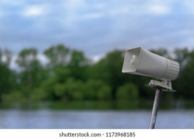 White megaphone on a mast against nature scene with a lake water, forest and blue sky