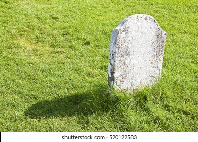 White memorial stone lying on a green grass field - image with copy space