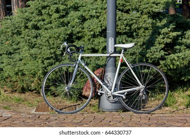 White men's bicycle against a metal pole on a paved road with a knapsack attached to it