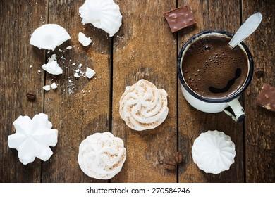 white meringue on a dark wooden background with retro metal coffee mug