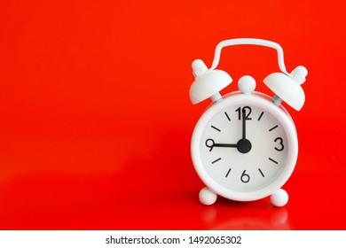White metal alarm clock on a white background. Nine o'clock. Copy space