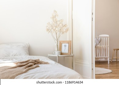 White metal bedside table with coffee mug, twig in glass vase and simple poster in frame placed by the bed in real photo of white bedroom interior