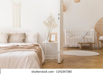 White metal bedside table with decor and coffee mug placed by the bed in bright bedroom interior with door to newborn baby room with crib