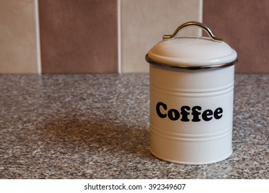 A white metal canister for storing coffee on a granite kitchen worktop with brown and beige tiles in the background.