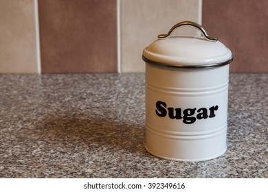 A white metal canister for storing sugar on a granite kitchen worktop with brown and beige tiles in the background.