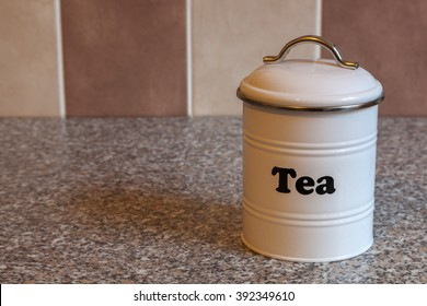 A white metal canister for storing tea on a granite kitchen worktop with brown and beige tiles in the background.