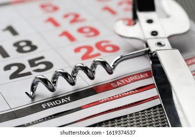 white metal corkscrew and calendar. Weekend concept