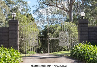 White metal driveway entrance gates set in brick fence leading to rural property with eucalyptus trees in background