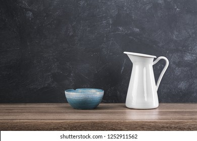 White metal jug and blue bowl on rustic wooden table against shabby grey wall. crockery.