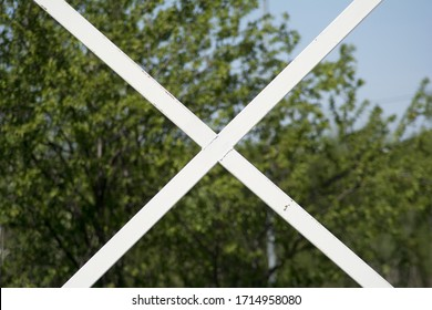a white metal profile fence, a detail in a shape of letter x