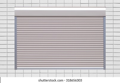 White metal roller window shutter and white brick wall
