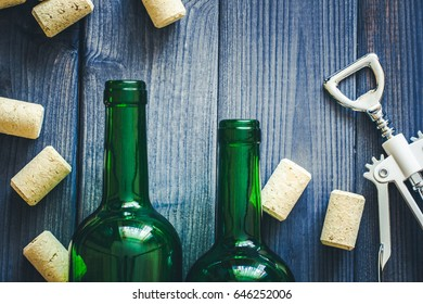 White metal wine opener on blue wooden table with green empty wine glass bottle and corks.