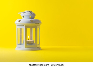 White metallic lantern with burning candle over yellow background, copy space
