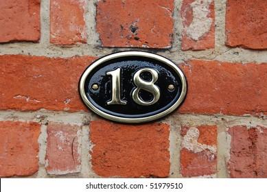 white metallic number (18) hanging a brick wall