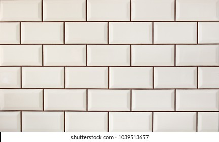 White metro tiles patterned wall. Beige ceramic brick tiles background.