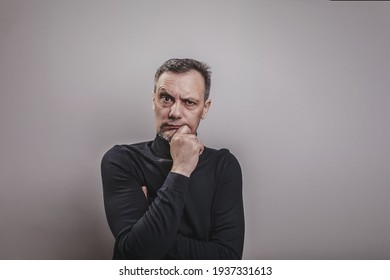A white middle aged man of European appearance with gray in his hair and a slightly unshaven face in a black turtleneck looks menacingly forward with his chin propped on his hand