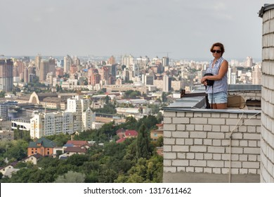 White middle aged tanned woman stands on the roof of a tall building with aerial cityscape in Kiev, Ukraine.