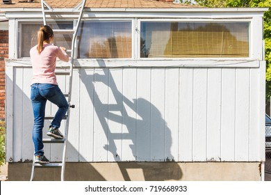 White, middle aged woman climbs ladder on edge of old urban home