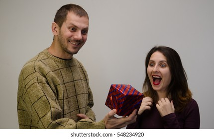 White middle-aged man gives his sweetheart, beautiful woman a gift in a box. She looks truly happy and exiting.