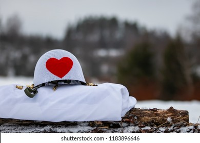 White military helmet with big red heart. It's winter. The picture also shows gunshot shells.