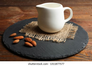 White milk jug and almonds nuts on slate board on wooden background. Concept almond milk.