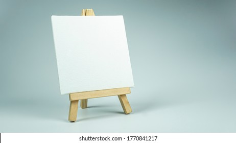 white mini canvas on a small wooden easel stand
