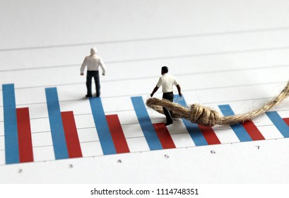A white miniature man standing on a bar graph and a black miniature man wrapped in rope.